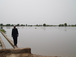 A man walking on a concrete barrier near a flooded area.