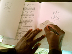 A pair of hands scribbling on a blank page in a book.