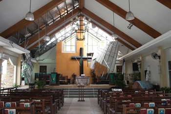 UCCP church in Tacloban with its roof peeled back and side windows blown out.