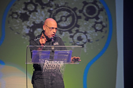 The Rev. Tony Campolo speaking from a lectern on a stage.