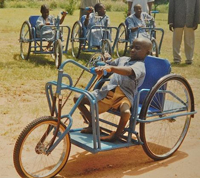 A young Nigerian afflicted with polio is given a free hand-cranked bicycle/wheelchair he can ride to school.