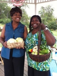 Two women holding baskets of produce.
