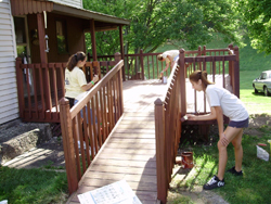 Carpenters work on a ramp leading to a porch.