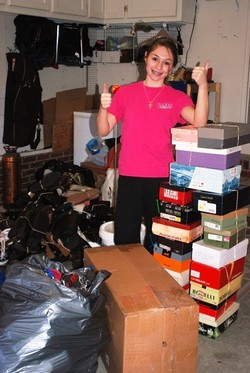 Girl standing with shoe boxes and shoes