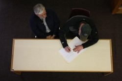 John Holst (left) and  Bob Banghart sign a document giving the former college's archives to the State Division of Libraries, Archives and Museums.