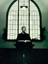 A black and white photo of Walter Soboleff, standing from a pulpit under a stained glass window.