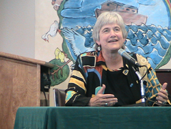 The Rev. Jane Adams Spahr, sitting on the stand during trial in front of a mural painted with a ship sailing on water, speaking.