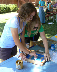 Two young women screen pressing paint over a t-shirt.