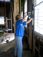 A woman using an electric nail gun to remove metal bars from a window.