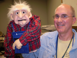 A man and a puppet, which appears to be of old age.