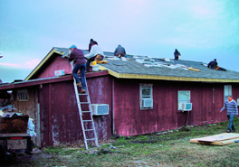 A group of people on a roof of a red-colored house, working.