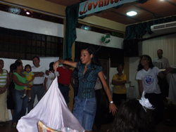 A  woman twirls a white sheet in the middle of a crowd