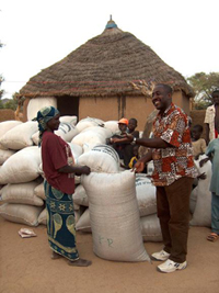 A group of people near near a village house surrounded by large bags of grain.