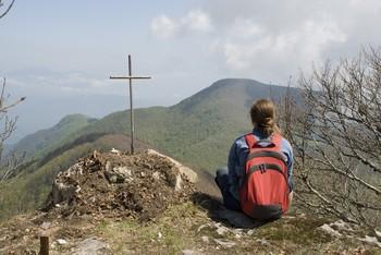 a young woman sits on a mountain looking a cross
