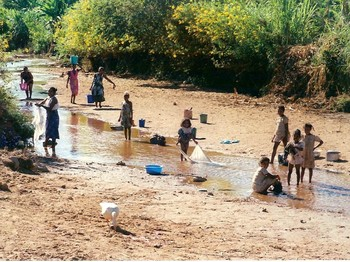 Women and children in Madagascar gather water and wash clothes in a stream far from their village. Lack of access to clean, abundant, and close water also contributes to poverty and vulnerability to being trafficked.