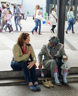 Michelle Lori meeting with a Syrian woman resting on the curb at the Keleti train station in Budapest.
