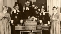 Donated food is blessed before being distributed. Sunday school children dressed as Puritans look on ― circa 1950.
