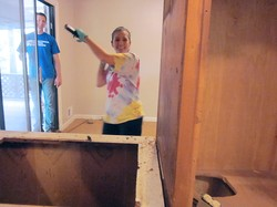 The Rev. Catherine Renken, pastor of Kirkwood Presbyterian Church, uses a sledgehammer to demolish the old kitchen in Promise House.