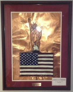 """Symbols of Freedom,"" bas relief on copper by Clyde Carter."