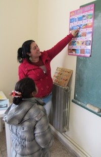 A Syrian girl reads a chart of English and Arabic words after her first month of attending school.