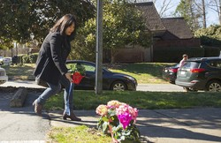 A woman places flowers near a building where three young Muslims were killed on Tuesday, in Chapel Hill, North Carolina on February 11, 2015.