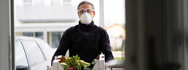 man carrying produce and wearing face mask and glasses
