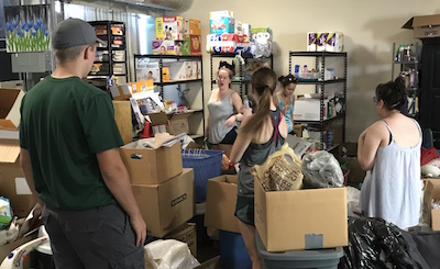 "Students from UKirk at Michigan State University sort through donations to the International Institute of St. Louis as part of their ""Hands and Feet"" experience."
