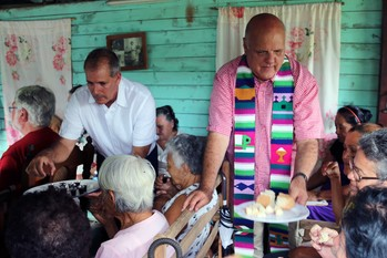 Ary Fernandez (left) and Edelberto Valdes serve communion to worshipers at the Presbyterian Mission at Marcane.