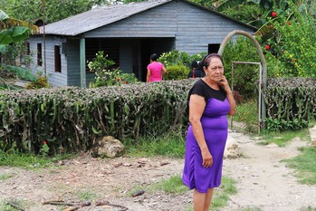 Cathy Reyes waits outside her home to greet worshipers at the Presbyterian Mission at Marcane.