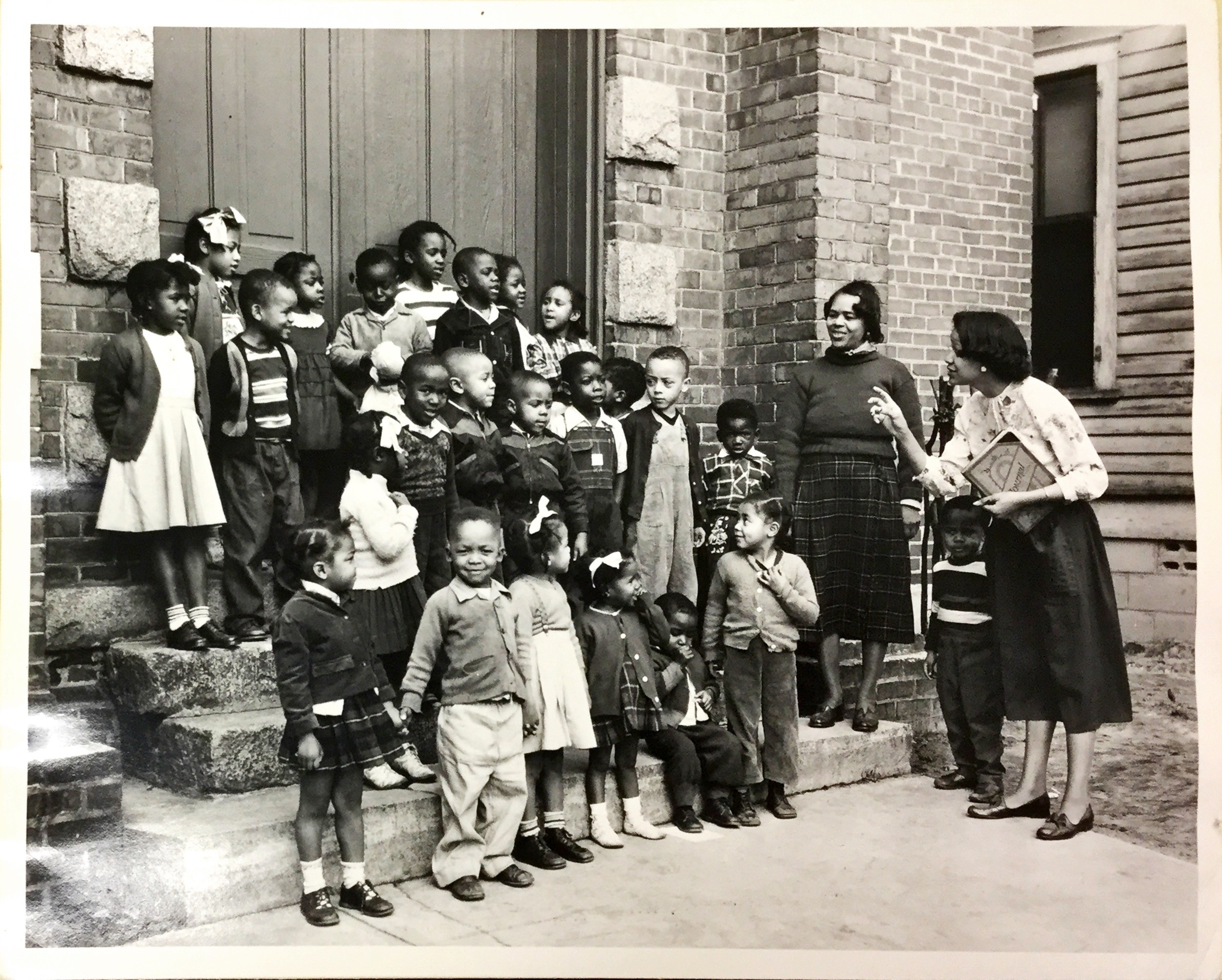 Mrs. Emily Ivory (widow of Cecil A. Ivory, superintendent of the nursery, leads the children of Hermon United Presbyterian Church in Rock Hill, S.C., in song. Cecil Ivory served the Hermon Church from 1949-1961, From congregational vertical file, RG425.