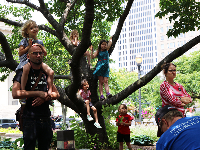 Those attending the End Cash Bail rally sought shade, and a vantage point, wherever they could find it.(Photo by Angie Stevens