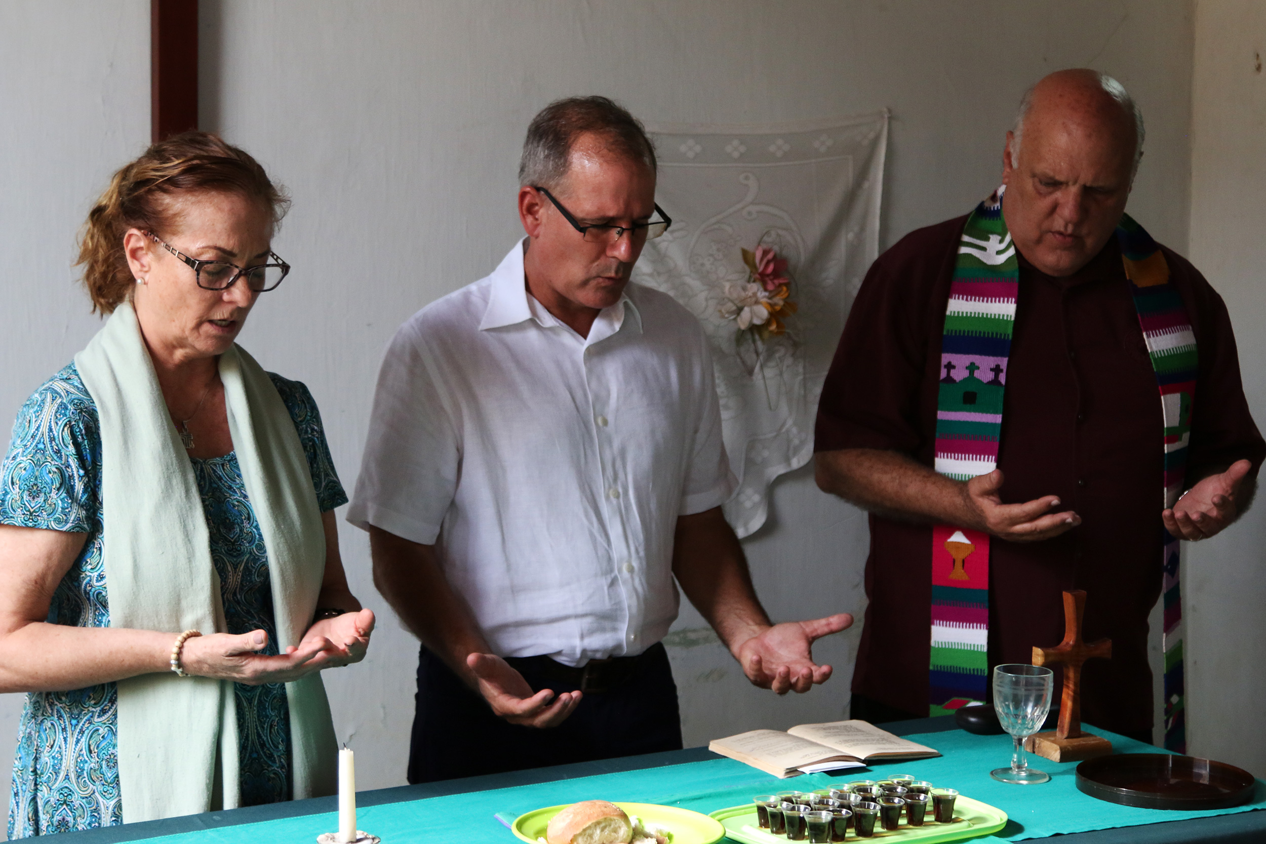 Jo Ella Holman (left), Ary Fernandez (center) and Edelberto Valdes (right) officiate for the Sacrament of the Lord's Supper at Camagüey Mission.