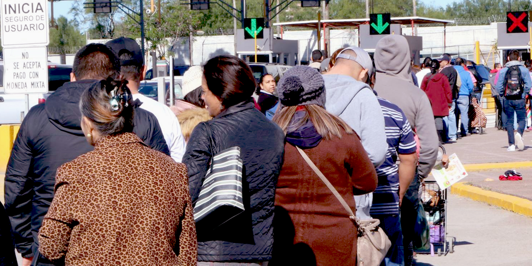 Image of people waiting in line at the border between Mexico and the United States.