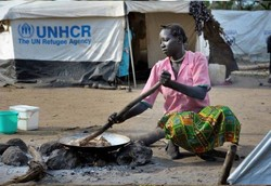 A South Sudan woman cooks in a refugee camp