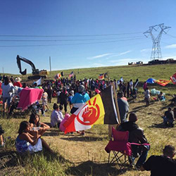 Protesters congregate next to a construction site for the Dakota Access Pipeline on Monday morning, as a crew arrives with machinery and materials to begin cutting a work road into the hillside. The flag in the foreground belongs to the American Indian Movement. (Photo by Daniella Zalcman)